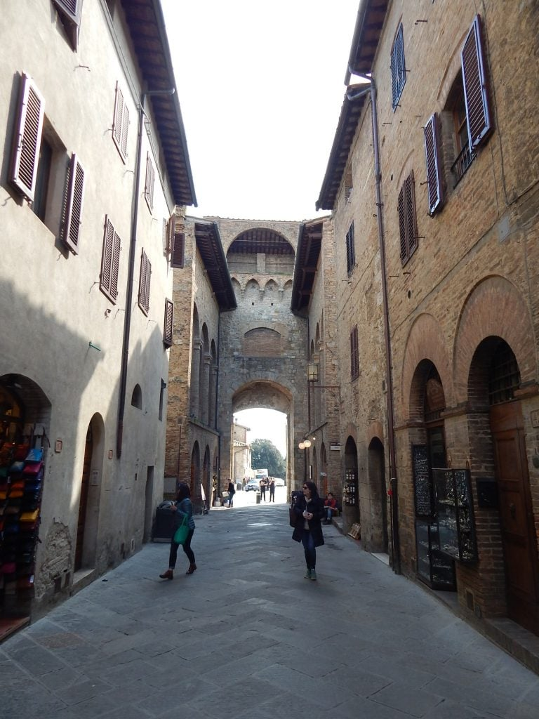 shows narrow street behind the town walls of San Gimignano in Tuscany