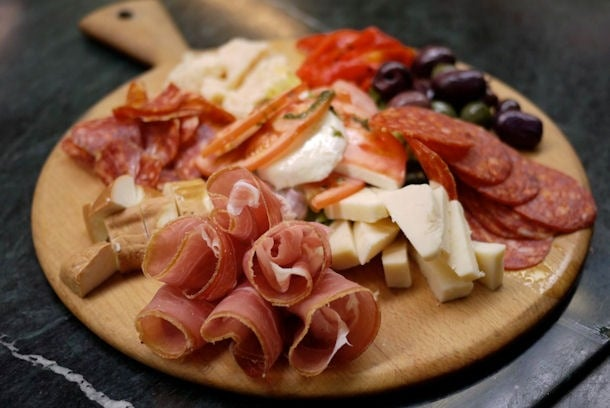 "Antipasto (or ""before the meal"") tray with cured meat, mozzarella, cheese , olives and bread"