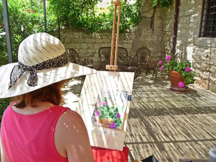 Woman painting flowering pot plant in the sun