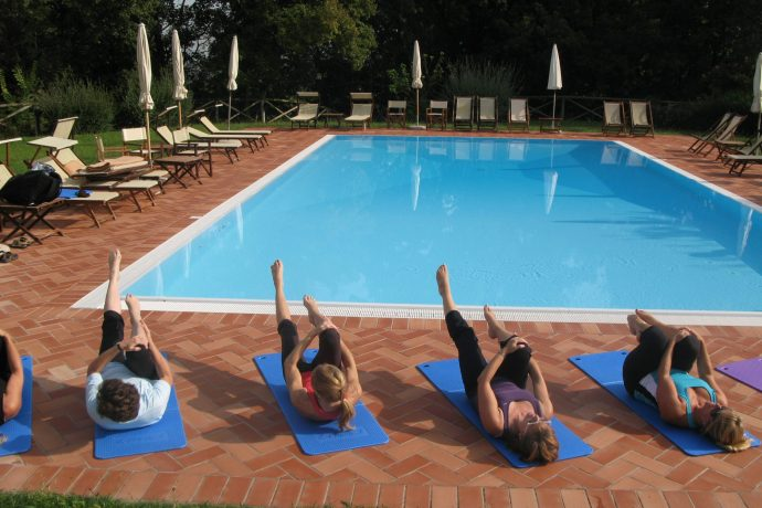 Group of Flavours guests doing Pilates beside the pool in Italy