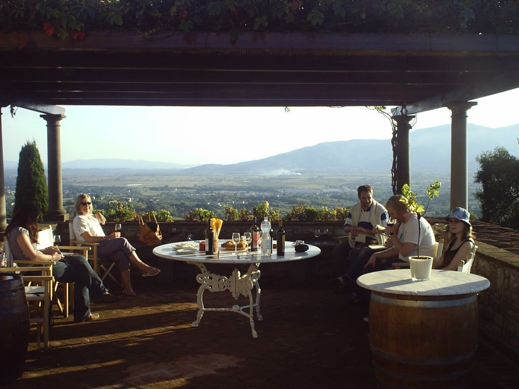 Group of Italian holiday guests around a white table with drinks overlooking an Italian mountain panorama