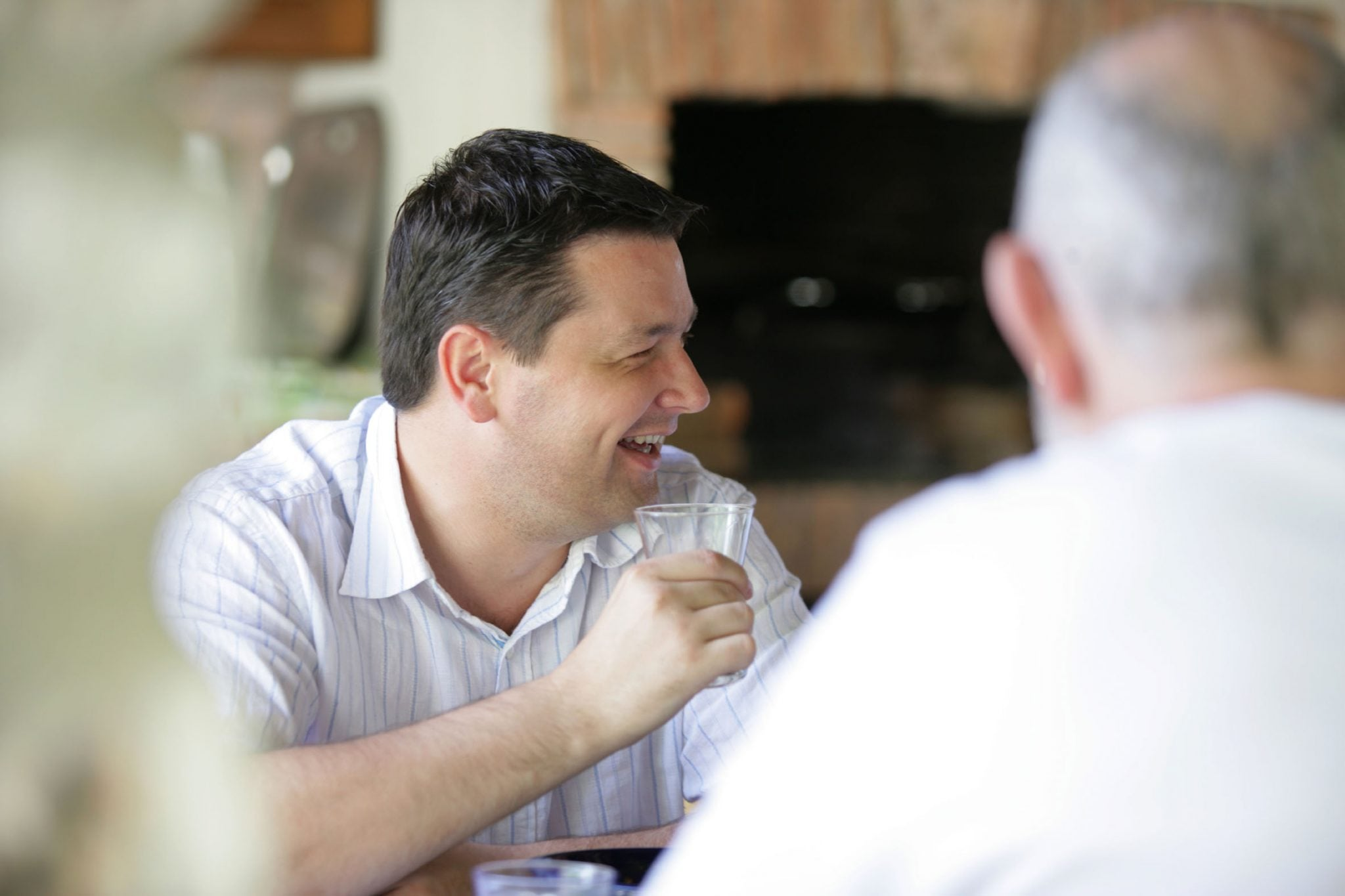 Man laughing with friends at lunch table