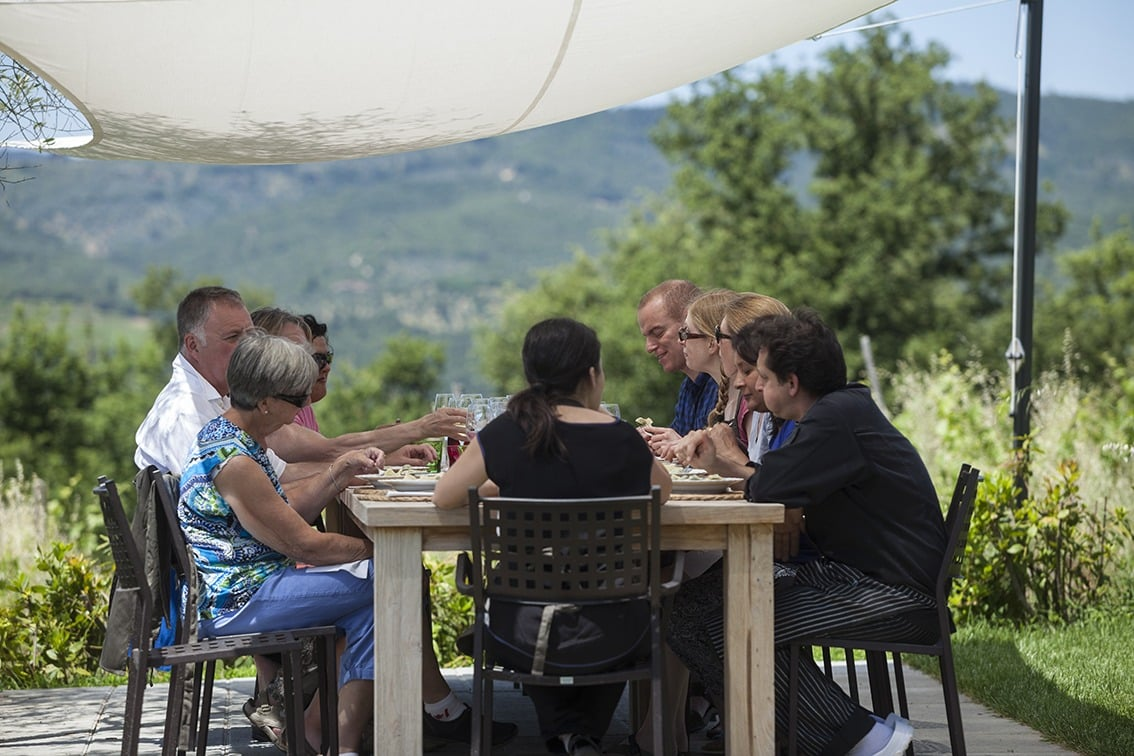 Group eating at an outdoor table under canopy in Tuscany