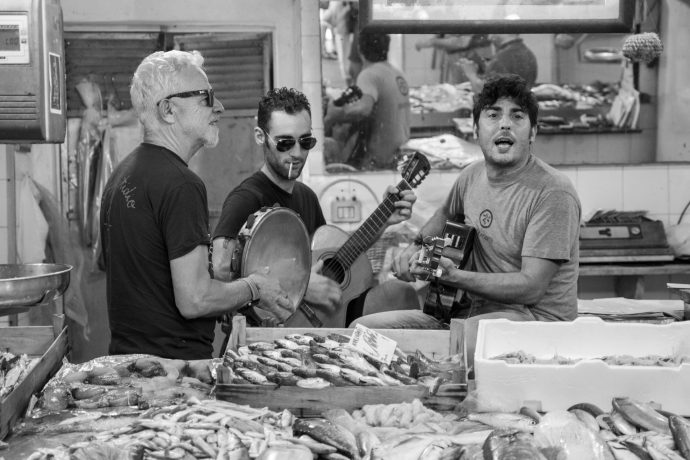 Three Italian men playing instruments in a fishmongers