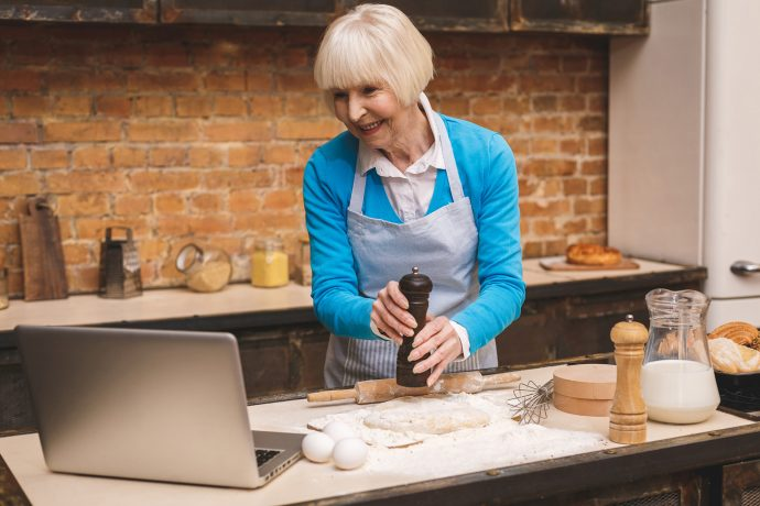 Woman taking part in online cooking class with laptop in her kitchen