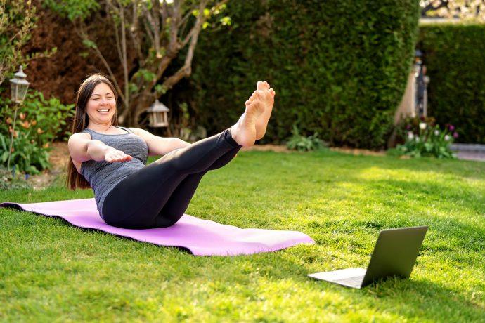 Woman Practising Pilates in front of Laptop in her Garden
