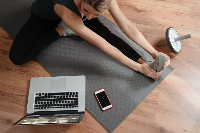 Woman Practising Pilates in front of Laptop in her Living Room