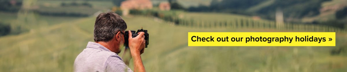 Man with camera clicking photos in a Tuscany farm and villa