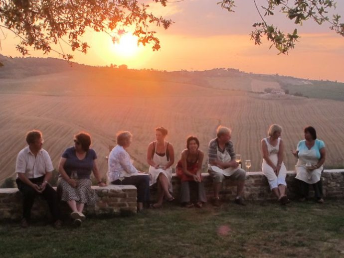 Solo travellers enjoying a glass of wine and sunset together
