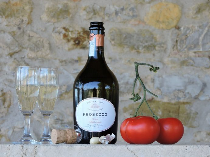 Open bottle of prosecco with two filled glasses resting on a wall