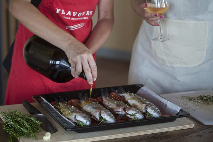 Flavours chef drizzling oil over a tray of prepared fish