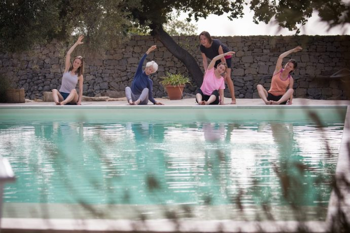 Pilates group stretching by the pool in Sicily