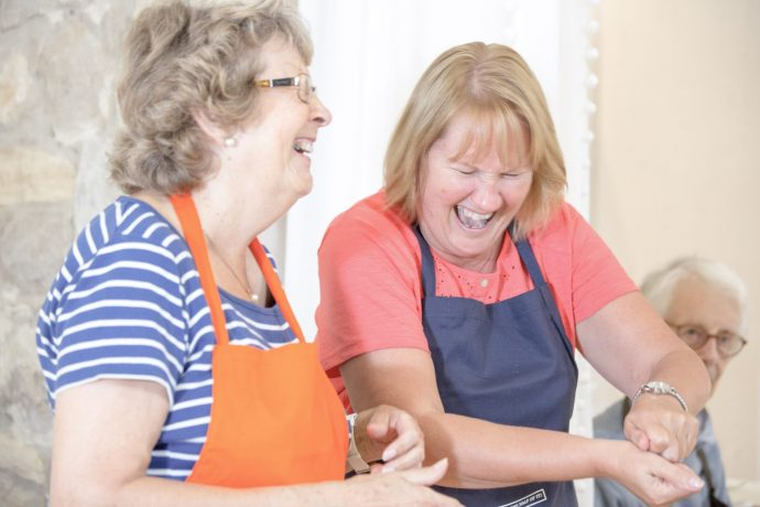 Two mature women laughing while cooking