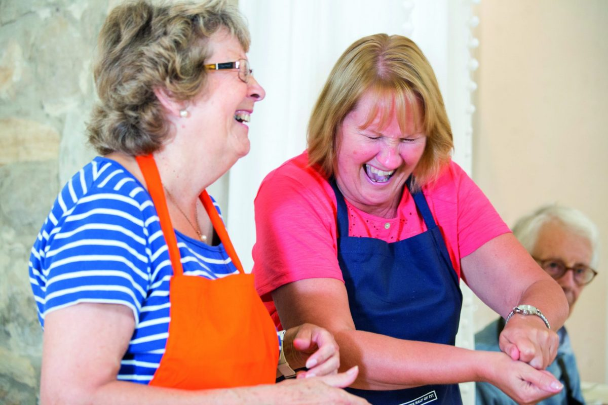 Two older women laughing together as they cook