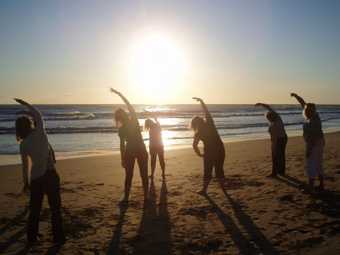 Group practicing Pilates on the beach at sunset