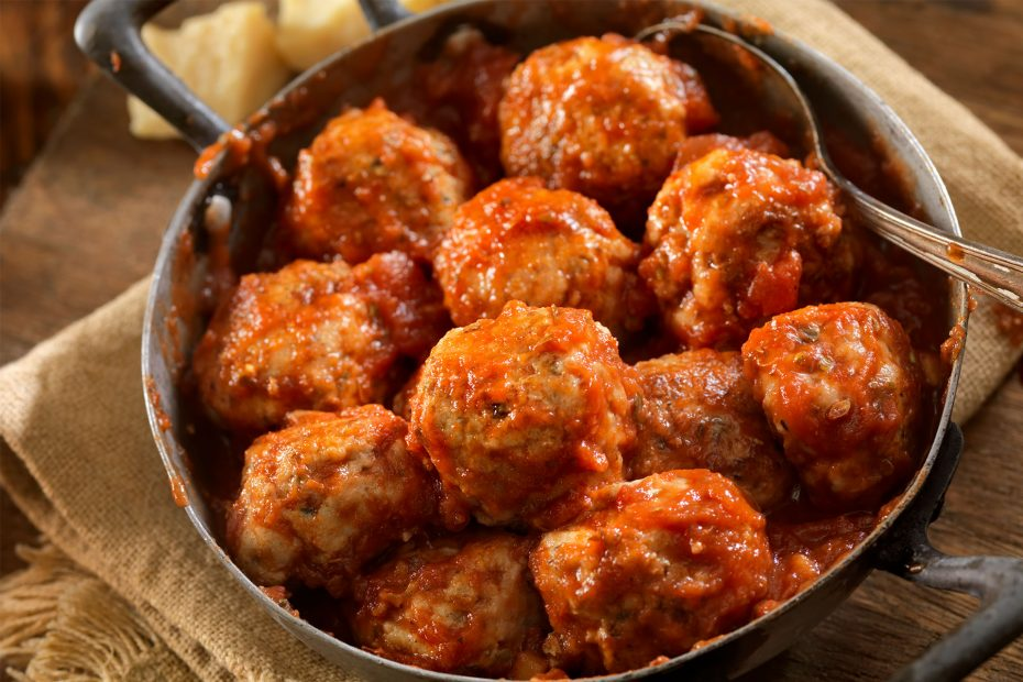 Italian meatballs being served in a pan