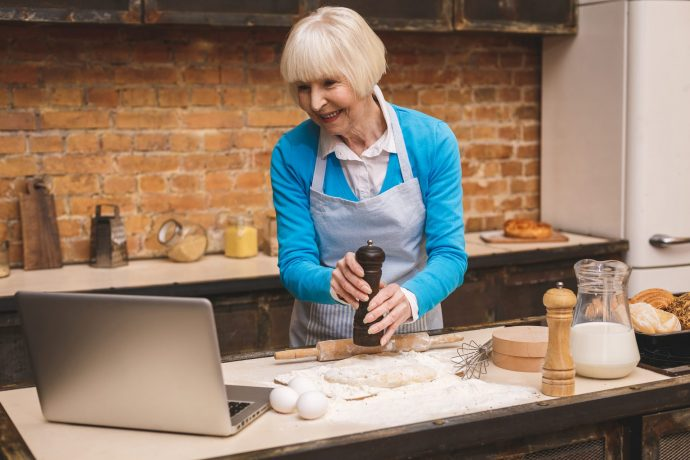 Woman cooking while taking part in an online cooking course