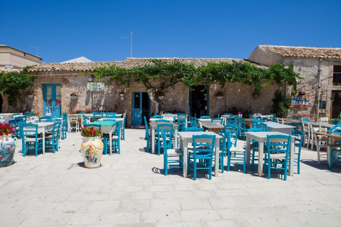 Sunny tables and chairs outside a restaurant in Sicily