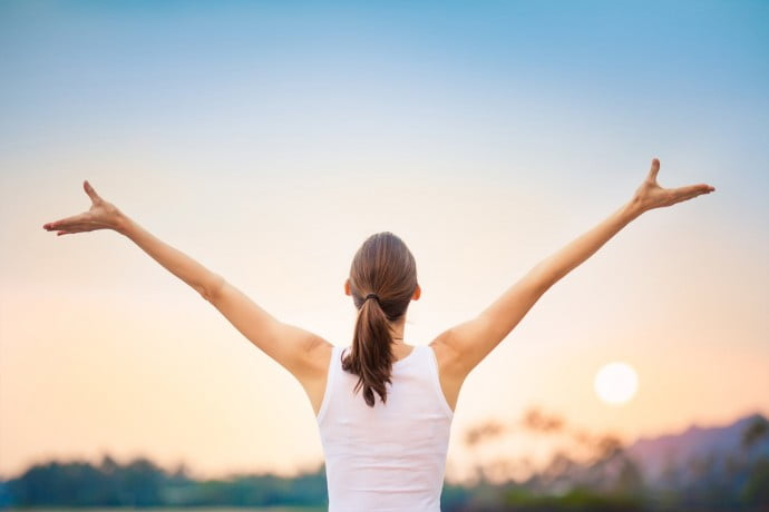 Woman wirh arms in the air after well being class