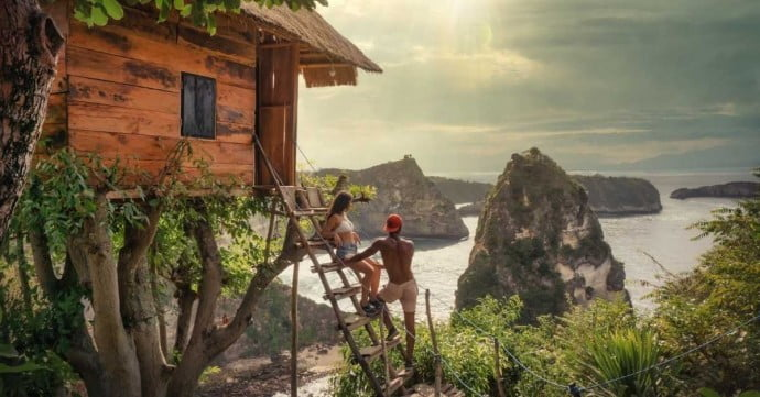couple looking at seaside view while staying at a treehouse