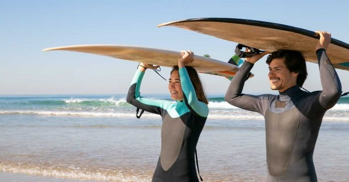 couple going to surf at the beach