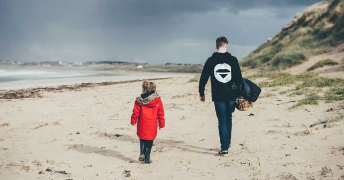 child and adult walking along the beach