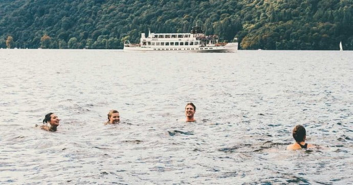 group of adults doing wild swimming in a lake