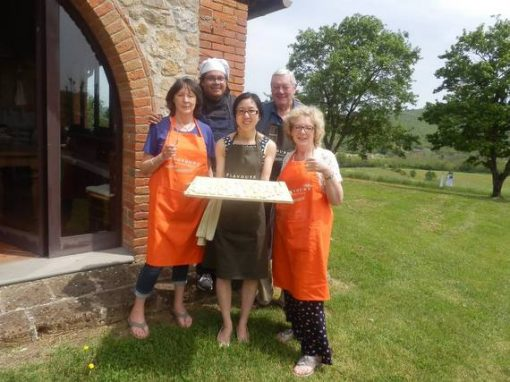 Cooking group in Tuscany presenting their home-made pasta outside in garden.