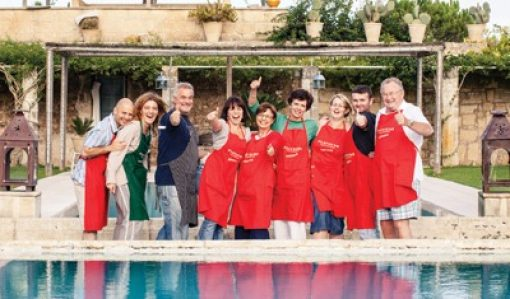 group of guests wearing aprons and laughing in front of the swimming pool
