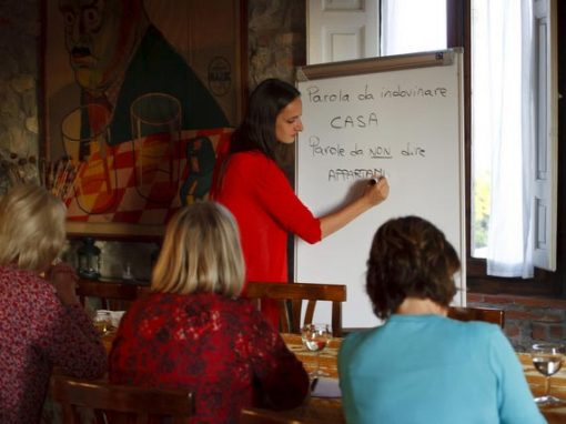 Italian language teacher with group of holiday guests teaching in local trattoria.