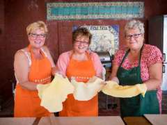 Three guests in apron preparing pizza dough.