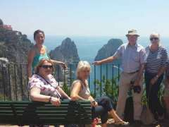 Guests standing on villa's cliffside terrace with stunning view