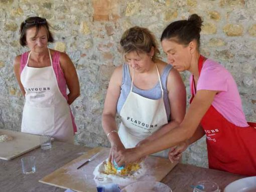 Female chef showing cooking guests how to prepare pasta dough.