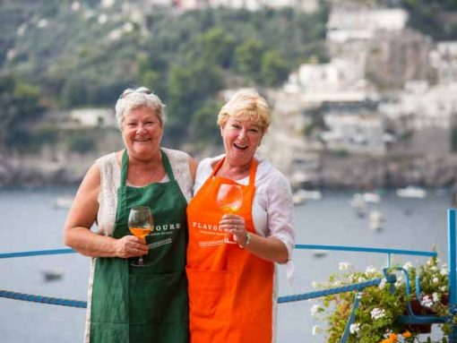 Two guests with aprons enjoying a glass of wine