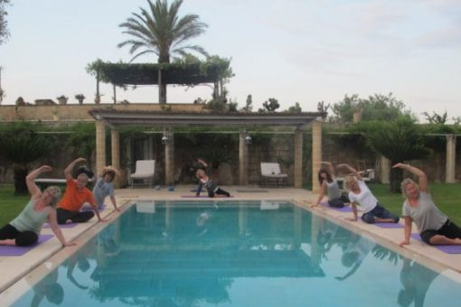 Pilates students in Puglia exercising outside at the pool