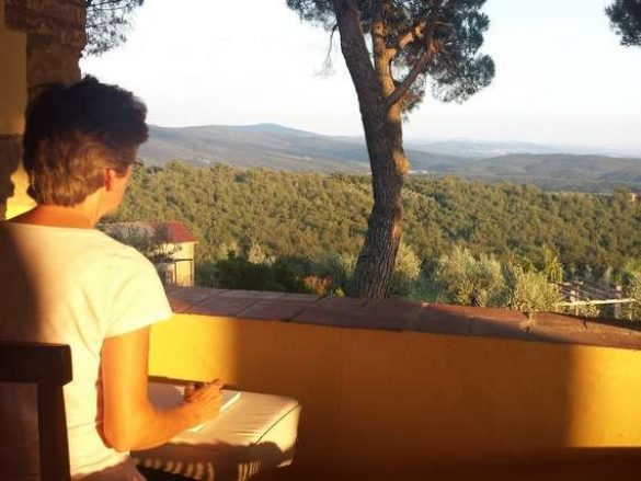 painting student in tuscany sitting on terrace with paper and brush ready to paint
