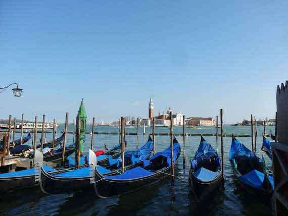 Venetian gondolas lined up in the water with view of Venice in the background.