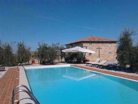 View of holiday villa and outdoor pool in Tuscan Chianti region.