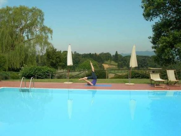 Pilates instructor showing Pilates pose by the pool in Tuscany