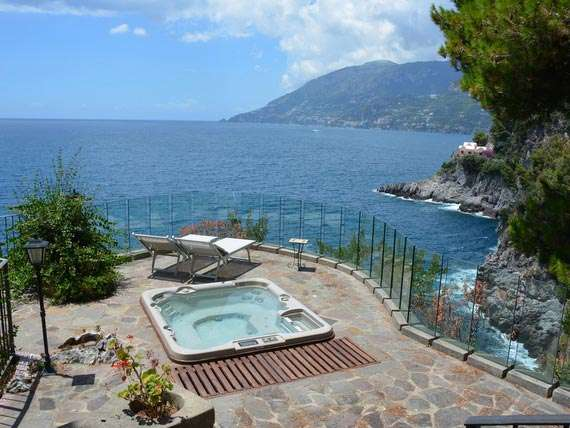 outdoor terrace of private holiday villa with spa and view of sea and cliffs