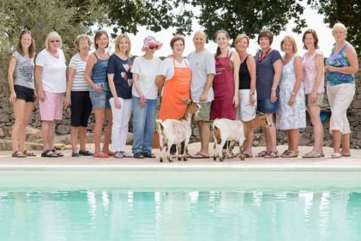 Happy Pilates guests standing at pool with two friendly goats