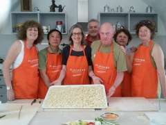 Guests with aprons standing in kitchen presenting tray of homemade orechiette.
