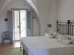 A spacious bedroom flooded with natural light in Puglia.