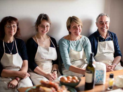4 guests with apron sitting on a bench in our venue's kitchen.