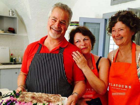 Italian chef Antonio and 2 female cookery guests in apron presenting freshly made cake in rustic kitchen.