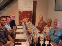 Group of painting students sitting around table in vineyward at wine tasting in Tuscany.