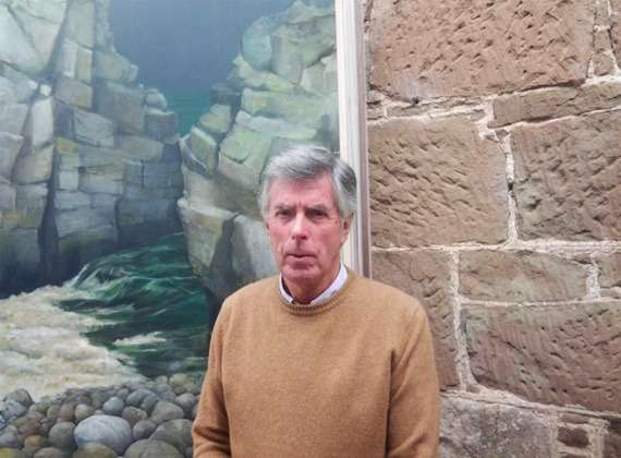 Painting teacher Ian Hamilton in front of a landscape painting.