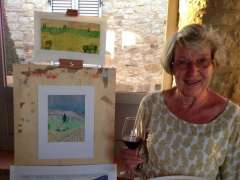 Mature lady with glass of wine next to easel and watercolour painting.