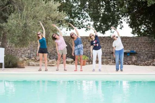 Five women standing at pool and doing Pilates pose.