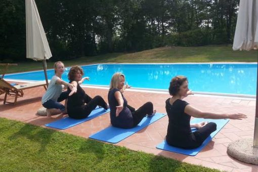 Pilates instructor helping guests by pool